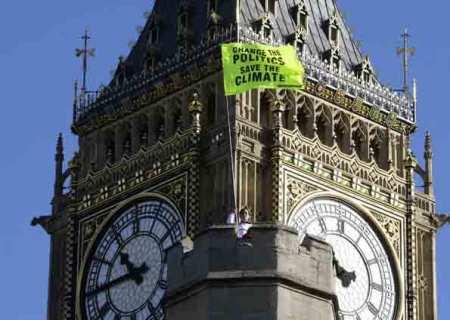 Manifestante balança bandeira em defesa do ambiente sobre o telhado do palácio Westminster, em Londres (Foto: Reuters)